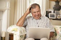 Hombre mayor jubilado frustrado que se sienta en Sofa At Home Using Laptop Fotografía de archivo