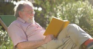 Hombre mayor jubilado que se relaja al aire libre leyendo un libro que disfruta del retiro almacen de video