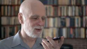 Hombre mayor moderno en casa usando el teléfono móvil, hablando con el amigo Estantes del estante para libros en fondo metrajes