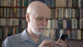 Hombre mayor moderno en casa usando el teléfono móvil, hojeando, leyendo Estantes del estante para libros en fondo almacen de metraje de vídeo