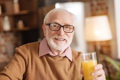 Hombre mayor optimista que presenta con un vidrio de zumo de naranja foto de archivo libre de regalías