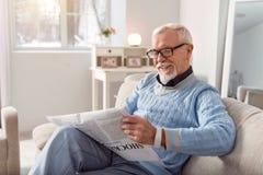 Hombre mayor optimista que sonríe mientras que lee el artículo en periódico imagenes de archivo