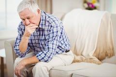 Hombre mayor preocupante que se sienta en el sofá Fotos de archivo
