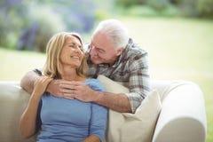 Hombre mayor que abraza a una mujer en sala de estar Fotografía de archivo libre de regalías