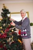 Hombre mayor que adorna el árbol de navidad Imagen de archivo