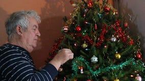 Hombre mayor que adorna el árbol de navidad almacen de video