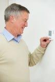 Hombre mayor que ajusta el termóstato de la calefacción central Imagenes de archivo