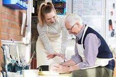 Hombre mayor que aprende utilizar la rueda de la cerámica con el profesor In Class Fotos de archivo libres de regalías
