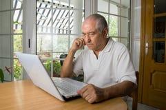 Hombre mayor que aprende utilizar un ordenador portátil Foto de archivo libre de regalías