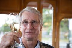 Hombre mayor que aumenta el vidrio de vino para una tostada Foto de archivo