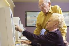 Hombre mayor que ayuda a la mujer mayor a utilizar el ordenador Foto de archivo