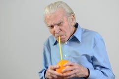 Hombre mayor que bebe el zumo de naranja fresco Imagen de archivo libre de regalías