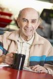 Hombre mayor que bebe la bebida caliente imagen de archivo