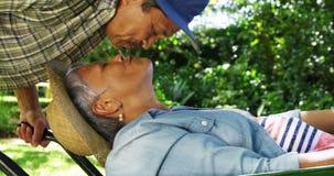 Hombre mayor que besa a la mujer en carretilla almacen de video