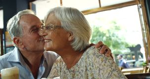 Hombre mayor que besa a la mujer mayor en el café 4k almacen de video