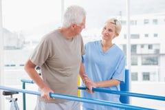 Hombre mayor que camina con ayuda del terapeuta Fotos de archivo