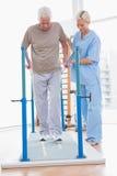 Hombre mayor que camina con ayuda del terapeuta Foto de archivo libre de regalías