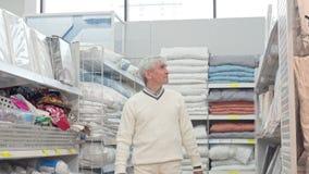Hombre mayor que camina en los grandes almacenes caseros, haciendo compras para el lecho almacen de metraje de vídeo