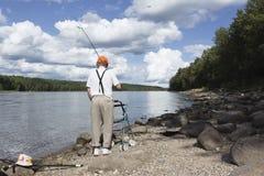 Hombre mayor que camina a lo largo de la línea de la orilla con el caminante y una caña de pescar sobre su hombro Fotografía de archivo