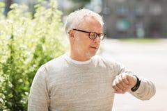 Hombre mayor que comprueba tiempo en su reloj foto de archivo libre de regalías