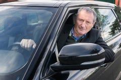Hombre mayor que conduce el coche Imagen de archivo libre de regalías