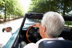 Hombre mayor que conduce el coche de deportes fotografía de archivo