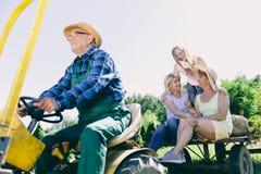 Hombre mayor que conduce el tractor remolque con su familia imagen de archivo