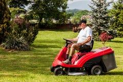 Hombre mayor que conduce un cortacésped rojo foto de archivo libre de regalías