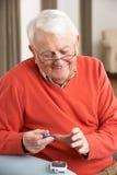 Hombre mayor que controla el nivel de azúcar de sangre Foto de archivo libre de regalías