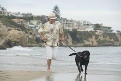 Hombre mayor que corre con el perro en la playa Fotos de archivo