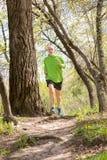 Hombre mayor que corre en el bosque Imagenes de archivo