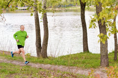 Hombre mayor que corre por el lago Imágenes de archivo libres de regalías