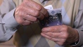 Hombre mayor que cuenta los billetes de banco euro, sueldos bajos, inseguridad social, primer metrajes