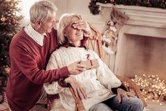 Hombre mayor que cuida que sostiene los ojos de la actual y cerrada mujer foto de archivo libre de regalías