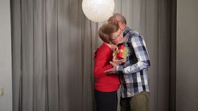 Hombre mayor que da el regalo de la tarjeta del día de San Valentín a su esposa almacen de video