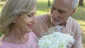 Hombre mayor que da las flores a la mujer querida, sorpresa agradable, atención, cuidado metrajes