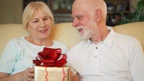 Hombre mayor que da a presente del aniversario del cumpleaños la caja de regalo de oro a la esposa Celebración del día del ` s de almacen de video