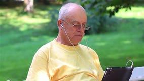 Hombre mayor que disfruta de música en su PC de la tableta