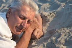 Hombre mayor que duerme en la arena imagen de archivo