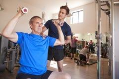Hombre mayor que ejercita con los pesos que son animados por el instructor personal In Gym fotografía de archivo libre de regalías
