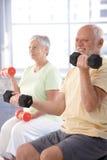 Hombre mayor que ejercita con pesas de gimnasia Fotos de archivo