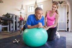 Hombre mayor que ejercita en la bola suiza que es animada por el instructor personal In Gym imágenes de archivo libres de regalías