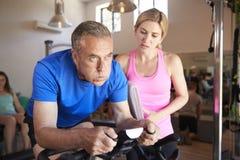 Hombre mayor que ejercita en la máquina de ciclo que es animada por el instructor personal femenino In Gym foto de archivo