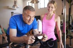Hombre mayor que ejercita en la máquina de ciclo que es animada por el instructor personal femenino In Gym imagenes de archivo