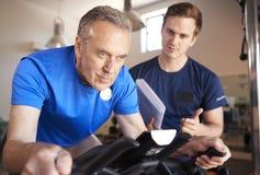 Hombre mayor que ejercita en la máquina de ciclo que es animada por el instructor personal In Gym imagenes de archivo
