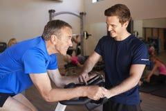 Hombre mayor que ejercita en la máquina de ciclo que es animada por el instructor personal In Gym fotografía de archivo