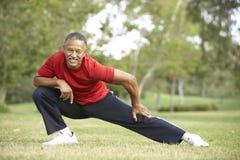 Hombre mayor que ejercita en parque Fotografía de archivo