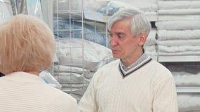Hombre mayor que elige mercancías del lecho con su esposa en la tienda del mobiliario metrajes