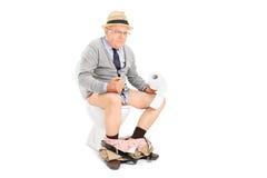 Hombre mayor que empuja asentado difícilmente en un retrete Fotografía de archivo libre de regalías