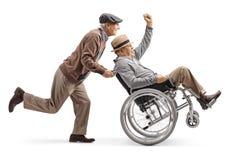 Hombre mayor que empuja a un hombre discapacitado positivo en una silla de ruedas que gesticula con la mano imagen de archivo libre de regalías